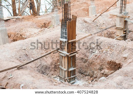Concrete pillar construction in site,Temporary wood forms are used to form concrete poured in place for foundation - stock photo