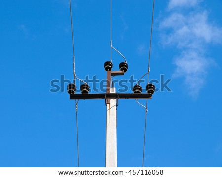 Concrete pillar of electricity transmission line with brown ceramic insulators. Photographed close-up against the blue sky - stock photo