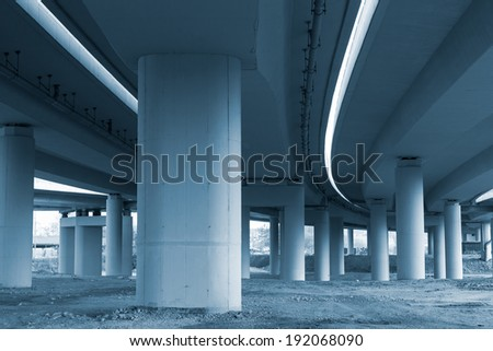 Concrete road curve and pillars under the viaduct - stock photo