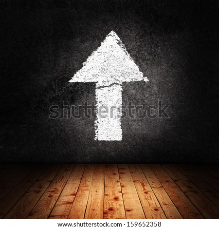 Concrete room with arrow on the wall pointing upward - stock photo