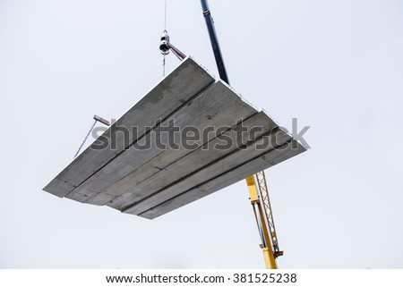 concrete slabs in the construction site using a crane. - stock photo