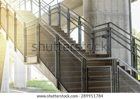 Concrete stairs are metal handrails with orange sunlight - stock photo