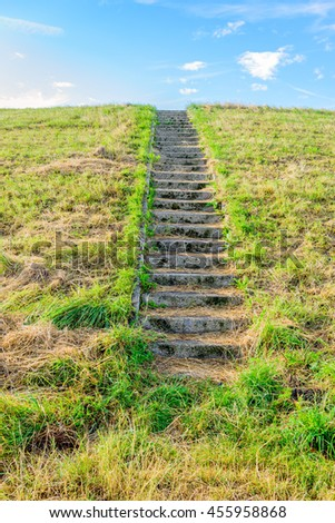 Concrete stairs to the top of a dike in the Netherlands. On the steps is yellowed grass. It's a sunny day in the summer season. - stock photo