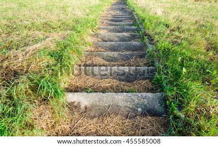 Concrete stairs to the top of a Dutch dike. On the steps is yellowed grass. It's a sunny day in the summer season. - stock photo