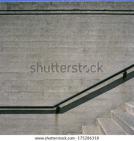 Concrete steps and iron railings with groove concrete wall - stock photo