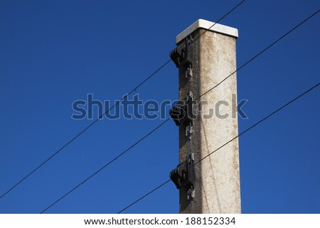 concrete support for electric fence against bright blue sky - stock photo
