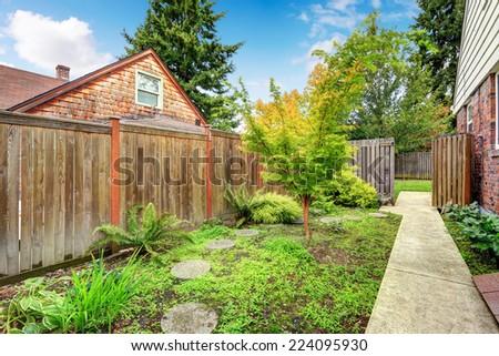 Concrete walkway leading to backyard area. HIgh wooden fence - stock photo