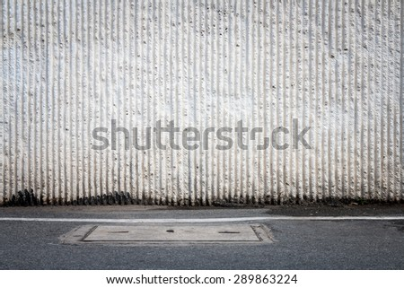 Concrete wall and asphalt road with manhole, traffic background - stock photo