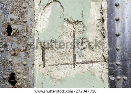 Concrete wall floor background with chips, crack, paint speckles, pale green paint, texture, white paint, steel, rivets, rust, holes - stock photo