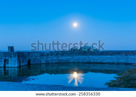 Concrete wall on the coast with the moon reflecting in a pool - stock photo
