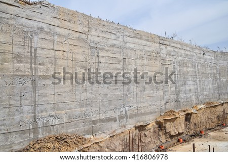 Concrete wall texture with wooden pattern impress from wooden form board shuttering and with sags of cement at construction site - stock photo