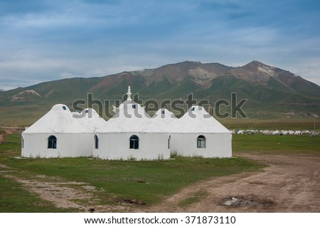 Concrete yurt in grass field in front of mountain on summer blue sky day