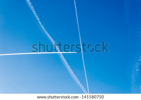 Condensation stripes from aircraft are white lines against the blue sky - stock photo