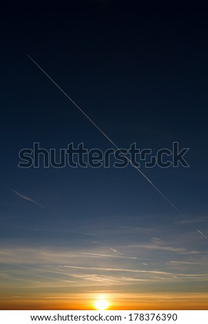 condensation trail in sunset sky  - stock photo