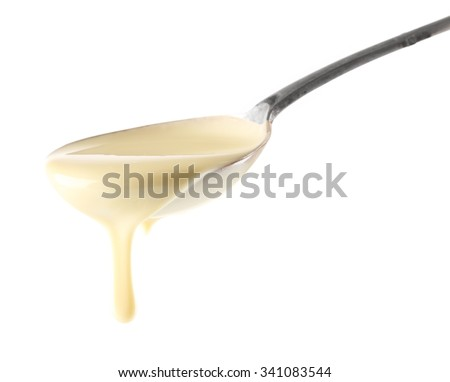 Condensed milk pouring from a spoon, isolated on white - stock photo