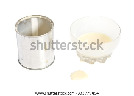 Condensed milk with sugar in glass bowl and tin can isolated on white - stock photo