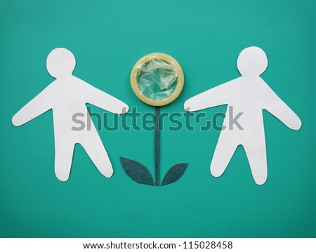 Condom and a pair of paper people on a green background. The metaphor of safe sex. - stock photo