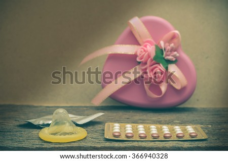 Condom and contraceptive pills on wood table - stock photo