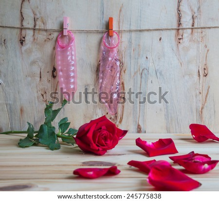 condom and red roses on clothesline over grunge background, Valentine concept