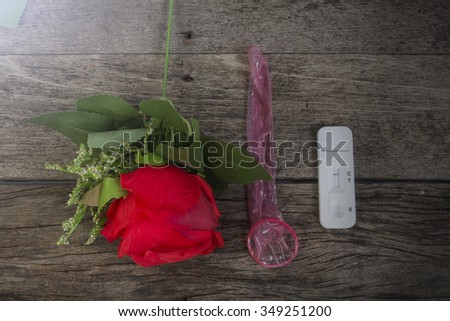 condom and red roses on wooden table background,Valentine concept