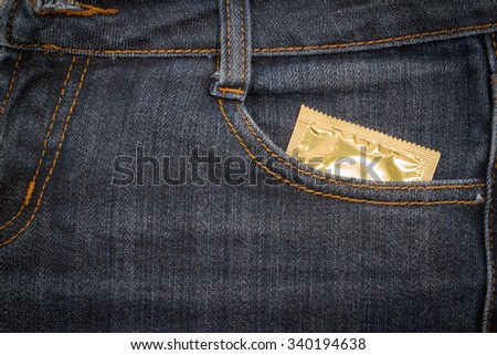 Condom in jeans pocket. Texture, background. - stock photo