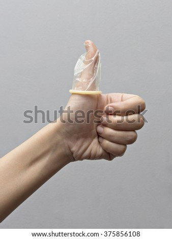 Condom on a woman finger - stock photo