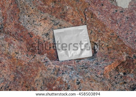 Condom surface. Silver condom lying on a rock - stock photo