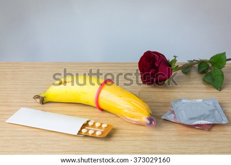 Condom with banana and contraception on wood background. Save Sex and Family plan and Prevention of sexually transmitted diseases and Valentine and contraceptive concept. - stock photo