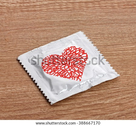Condom with heart on wooden table - stock photo