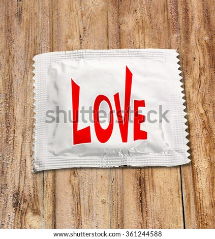 Condom with text Love on wooden table - stock photo