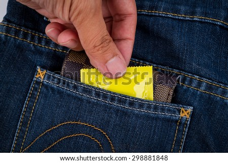 Condoms and billfold,in jeans pocket.Concept for Sexually transmitted infections (STIs) - stock photo