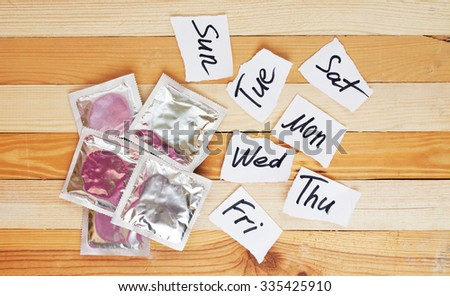 condoms and weekly pieces on wooden background. sex week protection concept  - stock photo