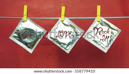 condoms hanging on clothespins, valentines day background. Sex, LOVE, Rock'n'roll poster design. selective focus image - stock photo