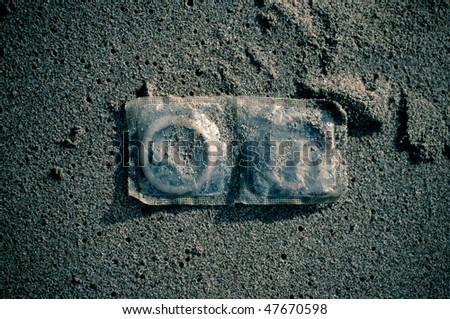 Condoms in sand - stock photo