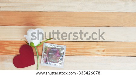 condoms, white rose and red heart on yellow background. dating concept image.Top View of Valentine's Day  light soft image - stock photo