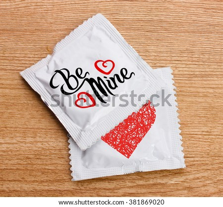 Condoms with text Be mine on wooden table - stock photo
