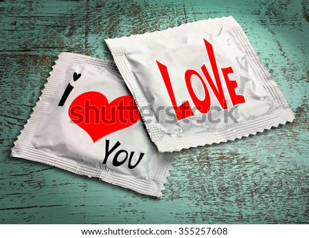 Condoms with text on wooden table - stock photo