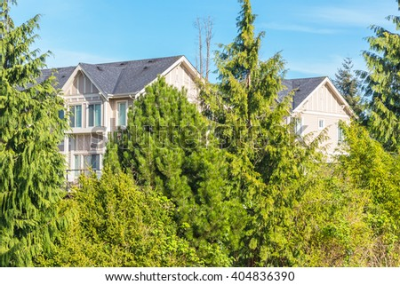 Condos behind trees in a residential neighborhood in Canada. - stock photo