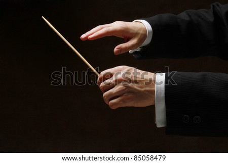 Conductor conducting an orchestra isolated on black background