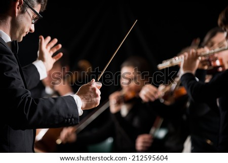 Conductor directing symphony orchestra with performers on background. - stock photo