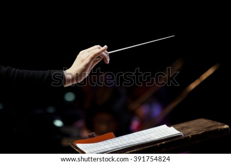 conductor's hand on a black background  - stock photo