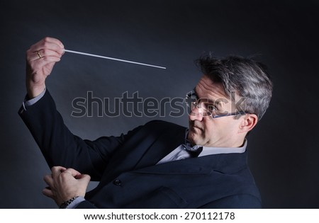 Conductor with a mad expression fidgeting with his baton - stock photo