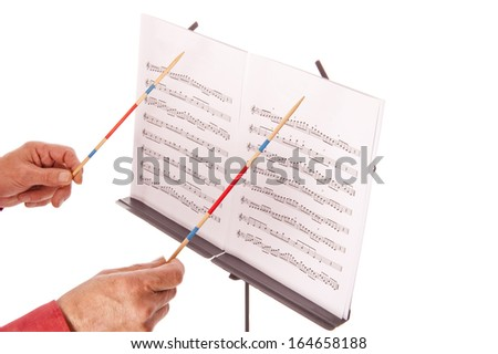 Conductor with baton directing melody from music sheet stand  - stock photo