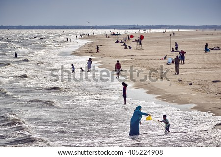 Coney Island, NY - June 23, 2014 : EDITORIAL - A Middle Eastern mother splashes water at her child, on the beach at Coney Island. - stock photo