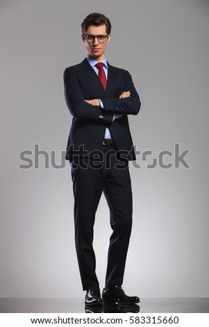 confdent business man standing with hands crossed, full body picture in studio
