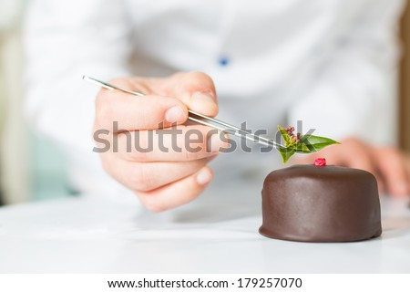 Confectioner putting the last ornament to a cake