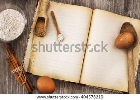 confectioner's recipe book and ingredients over wood with warm daylight