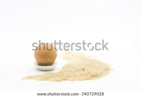 Confectionery of orange flavor. The candy ball coated with sugar on a mini white ceramic saucer.  Some brown sugar by the side on white background. - stock photo