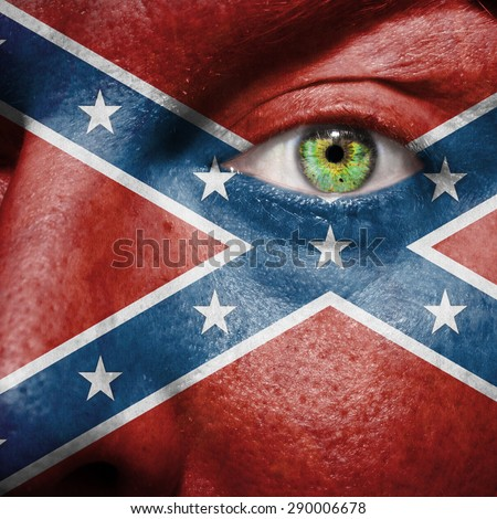 Confederate flag painted on a man's face. The flag is considered to be a rebel flag. The rectangular battle flag of the Army of Tennessee. - stock photo