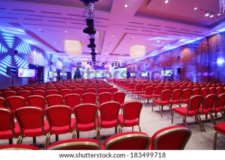 Conference  hall with red chairs and colored illumination - stock photo